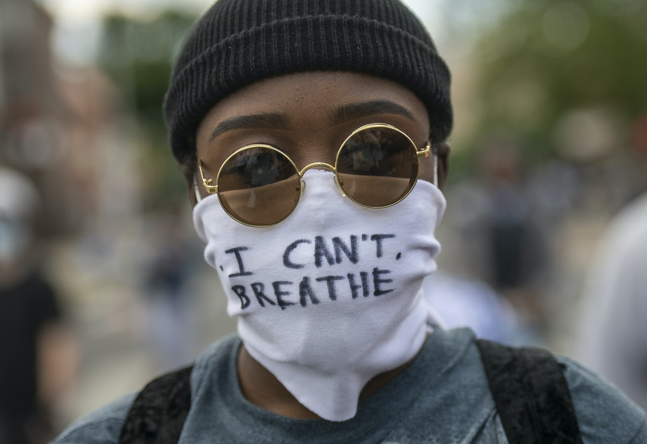 """caption: Protests over police treatment of black people have sparked concerns over the possible spread of COVID-19. Here, a protestor marches with a cloth mask stating """"I CAN'T BREATHE"""" in Philadelphia on Monday."""