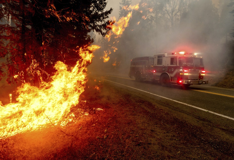 caption: A firetruck drives along state Highway 168 last month while battling the Creek Fire in the Shaver Lake community of Fresno County, Calif.