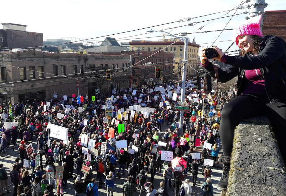caption: Elle Christensen watches 2017's women's march in Seattle from a perch at Seventh and Jackson.