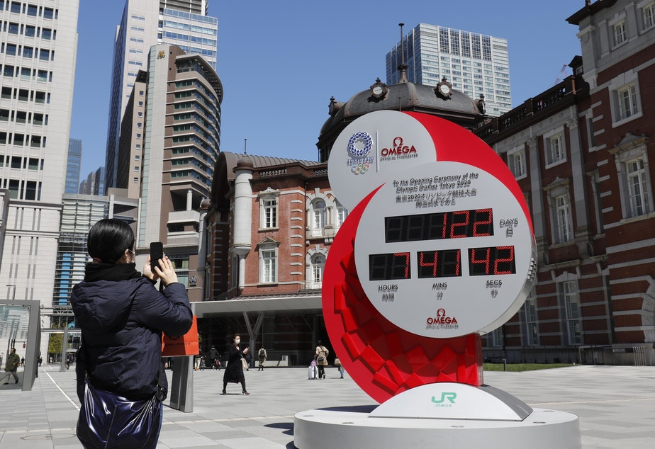 caption: The Tokyo Summer Olympics are being postponed until next year, the International Olympic Committee said Tuesday. Here, a person in Tokyo takes a photo of a clock counting down the days until the planned start of the Tokyo Games.