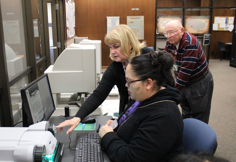 caption: Chelsea Craig, seated, looks through microfilm in the public research room of the National Archives in Seattle. A member of the Tulalip Tribes, Craig is searching for documents about the tribe's history. She is  assisted by volunteers Janice Hemingway and Dick Hall.