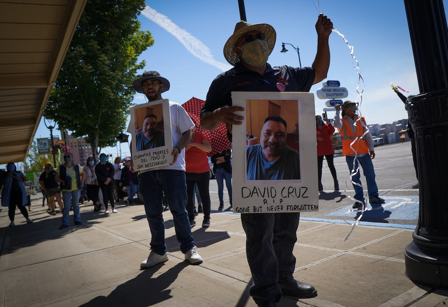 caption: Emmanuel Anguiano-Mendoza, left, and Agustin López hold posters featuring featuring David Cruz, a worker who died on May 30.Enrique Pérez de la Rosa/NWPB