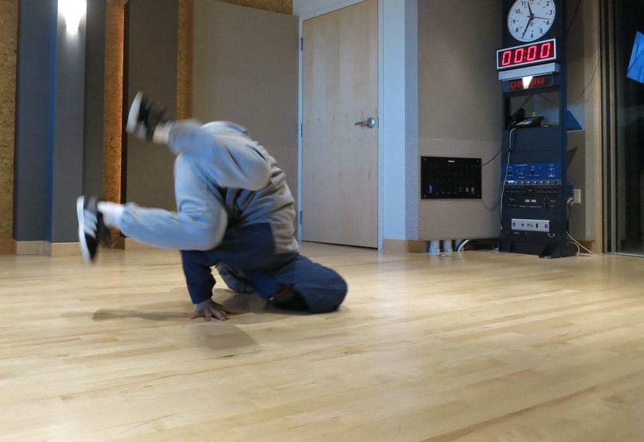caption: Krubel Amare shows off a head spin in the KUOW studio.