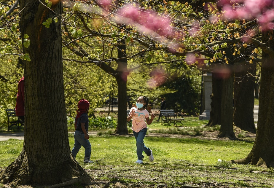 caption: A child wearing a protective mask plays in Brooklyn's Prospect Park in April.
