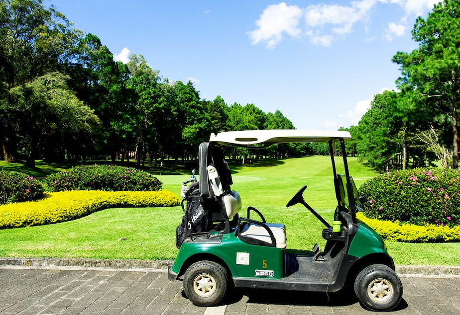 caption: Golf cart parked at a course