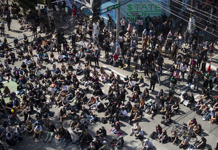 caption: A large crowd gathers at the intersection of East Pine Street and 12th Avenue, outside of the Seattle police department's East Precinct building, to listen to speakers on Wednesday, June 10, 2020, in Seattle.