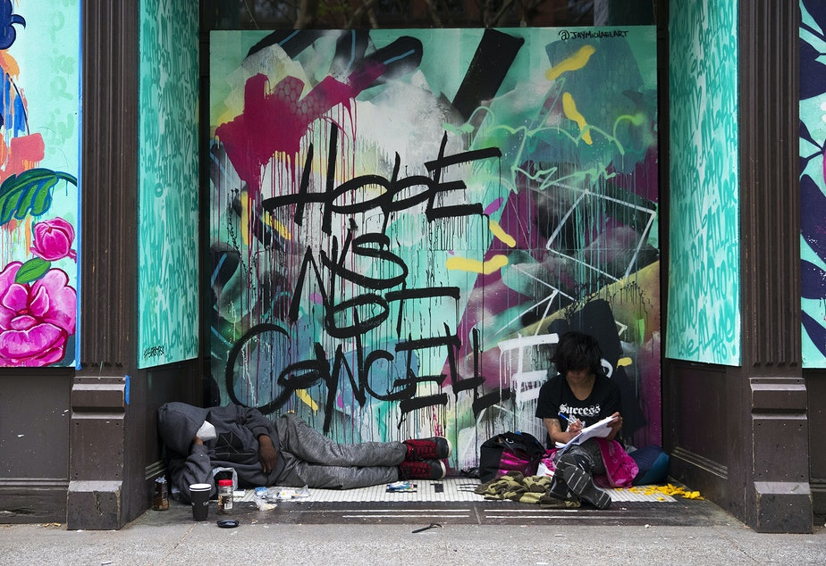 caption: Marty Jackson, left, and Gracie Ann, right, sit in the doorway of a boarded up business in front of a mural that reads 'Hope is Not Cancelled,' on Tuesday, April 28, 2020, along First Avenue South in Seattle.