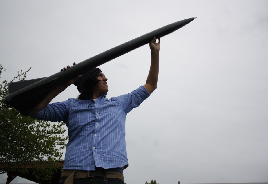 caption: Chris Cultee, a student at the Northwest Indian College, with a rocket that broke the sound barrier.