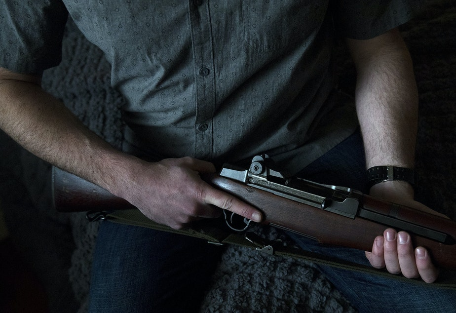 caption: Josh Young holds his M1 Garand firearm on Friday, February 21, 2020, at his home in Seattle.