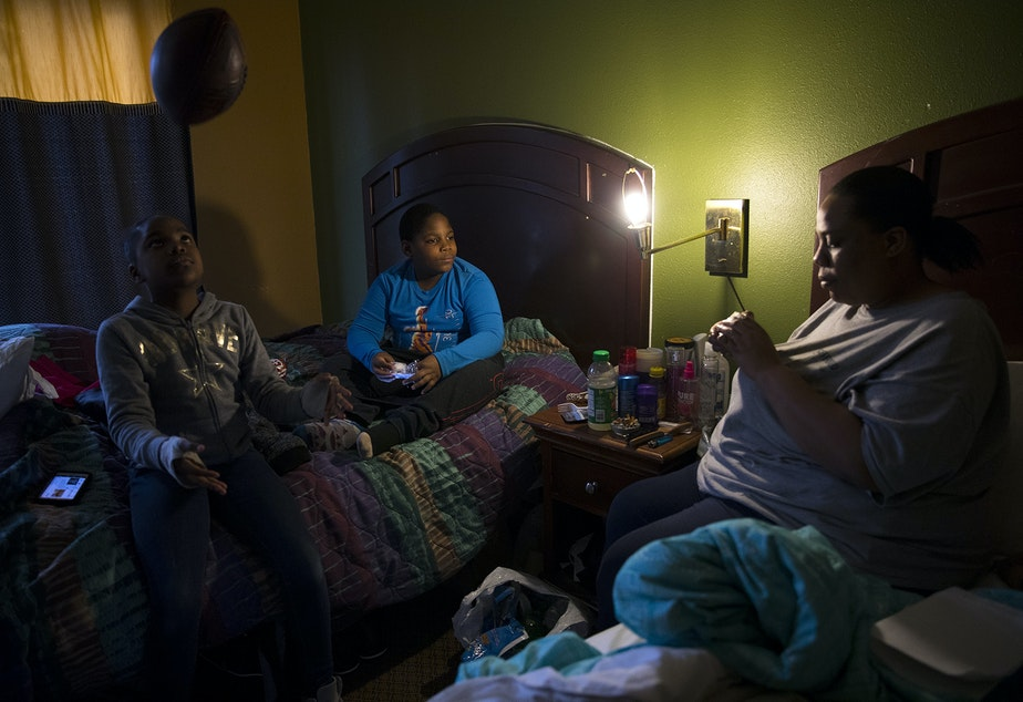 caption: Ja'Shay Macklin, 10, left, plays with a football as her twin brother Ja'Sean watches their mother Stephanie Macklin-Jones work on a rubik's cube in their room at the Everspring Inn on Monday, March 26, 2018, on Aurora Avenue North in Seattle.