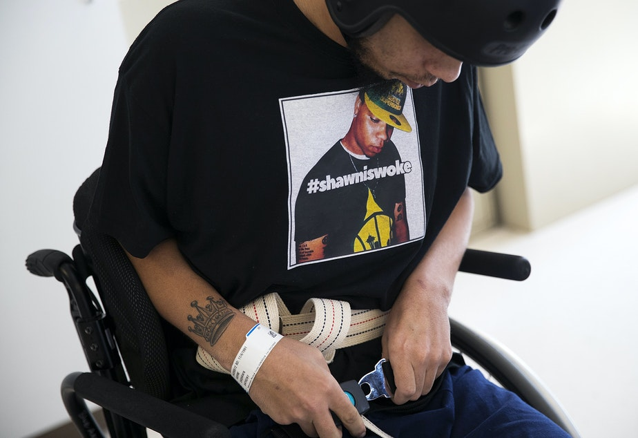 caption: DaShawn Horne buckles the belt of his wheelchair while wearing a t-shirt with his picture and the words #shawniswoke, on Thursday, April 19, 2018, during physical therapy at Harborview Medical Center in Seattle.