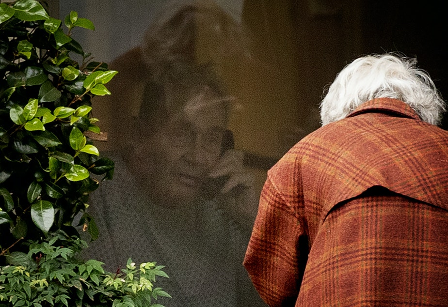"caption: Dorothy Campbell talks to her husband, Gene Campbell, on the phone through his window at the Life Care Center of Kirkland on Thursday, March 5, 2020, in Kirkland. Dorothy's son Charlie Campbell came from Silver City, New Mexico, to bring his mother to see his father. ""It's kind of tough but it's the best we can do at this point,"" he said."