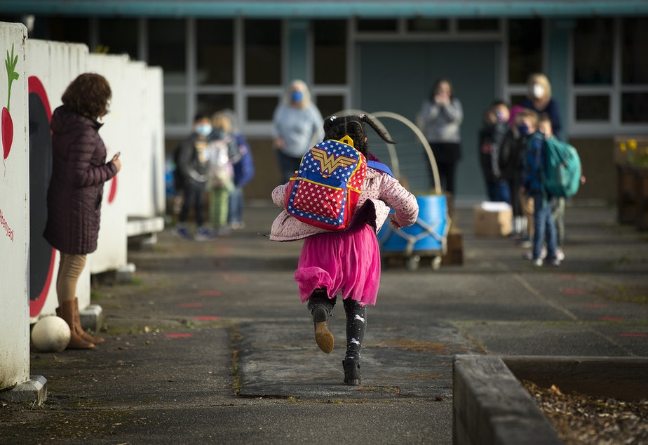 caption: Alayna Holmes, a first-grade student at Northgate Elementary, runs toward her classmates on Monday, April 5, 2021, on the first day of in-person learning at the school in Seattle.