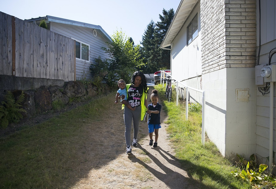 caption: Tiffany Montgomery walks to the overnight daycare facility to drop off two of her sons, 10-month-old Avalon Brown, left, and 5-year-old Curtis Brown, right, before working the night shift on Thursday, August 1, 2019, in Renton.