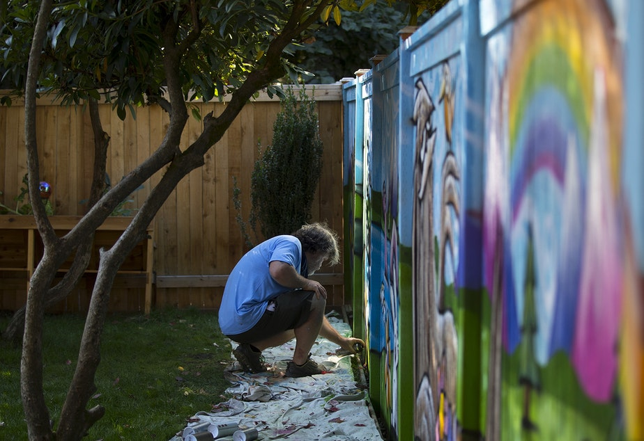 caption: Ryan Henry Ward works on a mural in the backyard of a home on Wednesday, September 8, 2021, in Shoreline.