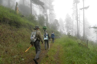David Calahan (left) and Chandra LeGue (center) hike up a trail in Southern Oregon. LeGue is carrying the Google Trekker to photograph the sights.