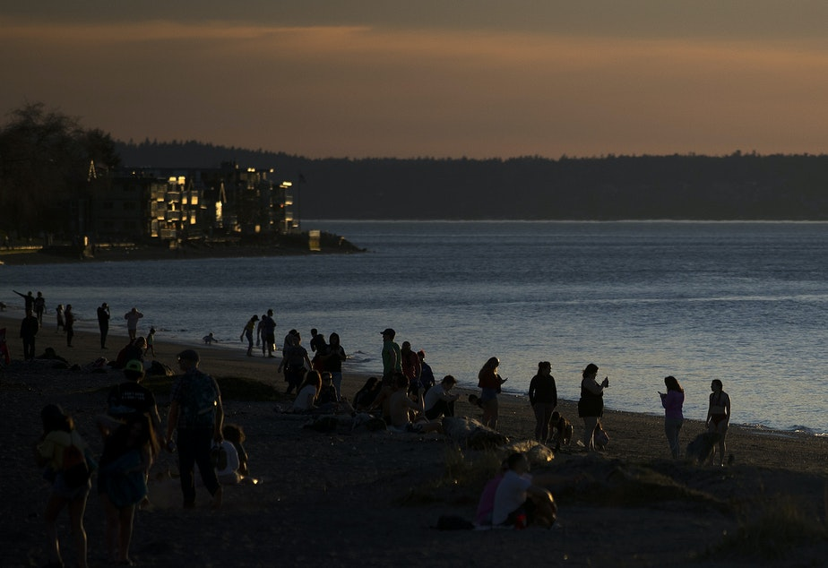 People gather to watch the sunset on Tuesday, March 19, 2019, at Alki Beach Park in Seattle.