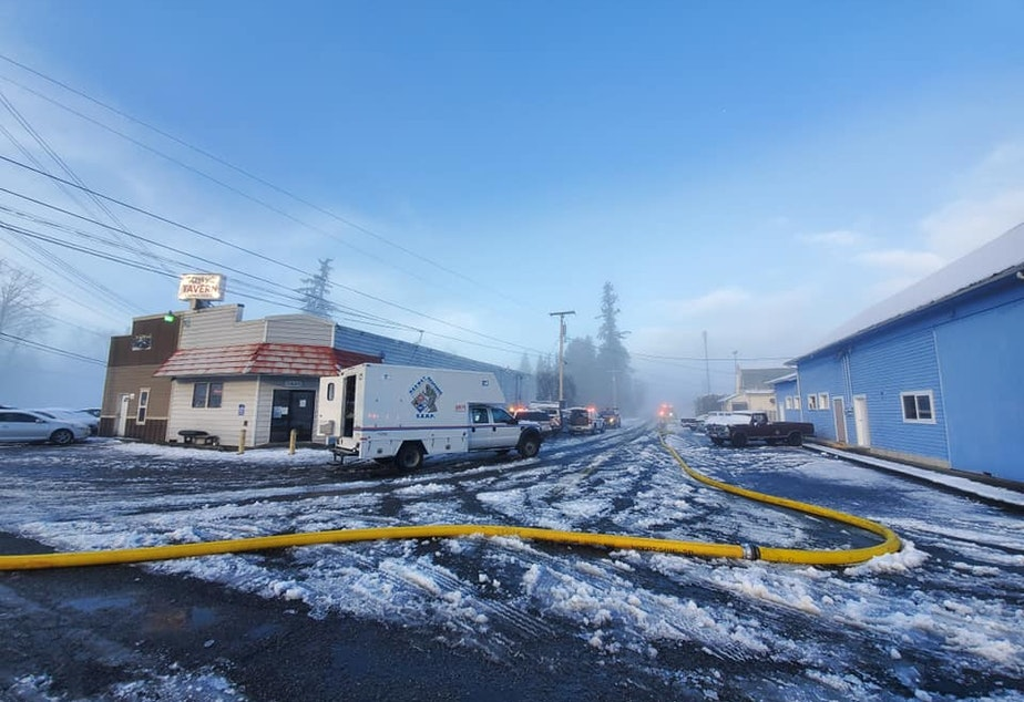 caption: A firefighting hose snakes through downtown Custer, Washington, on Dec. 22.