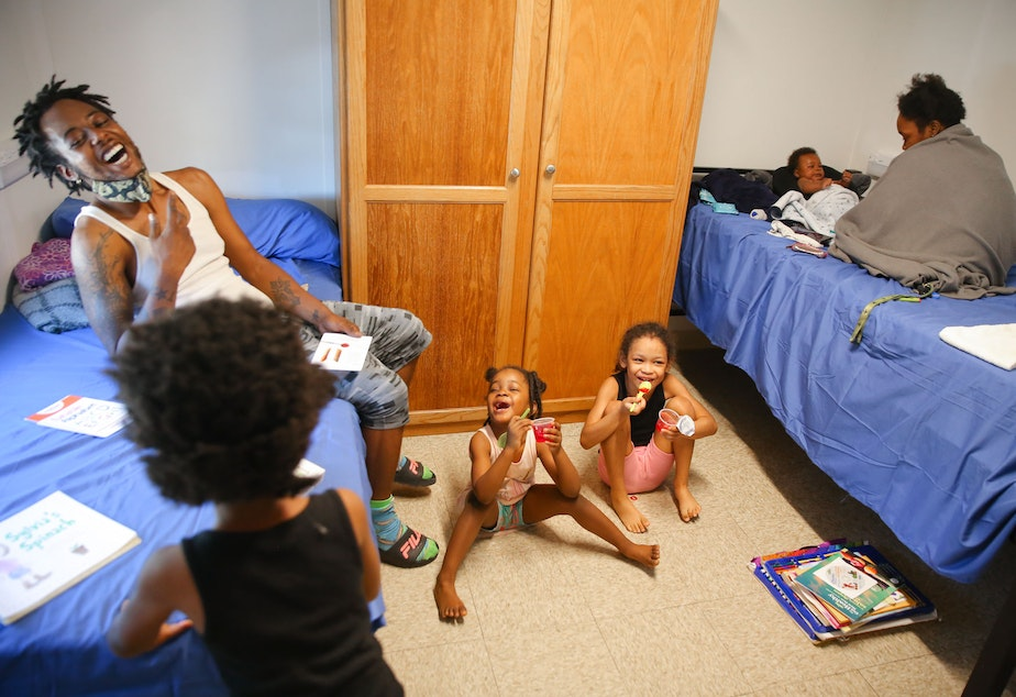 caption: Gregory Wraggs Sr. laughs with his daughters Av-ai, 5, left, Analiyze, 4, center, and Alycia, 8, as they eat jello, and his wife Shadoria Wraggs, right, plays with their two-month-old son Gregory Jr. inside their temporary room at the King County Cooling Center in White Center, Monday, June 28. The family has been living in their van for the past year and were able to stay in an air-conditioned unit at the cooling center this week as temperatures rose into the 100s.