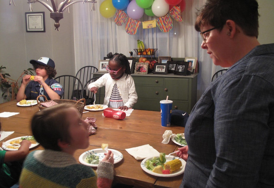Foster parent Mary Pico (right) eats dinner with her children and others gathered at her home for a monthly meeting of families in the Mockingbird Family Model of foster care.