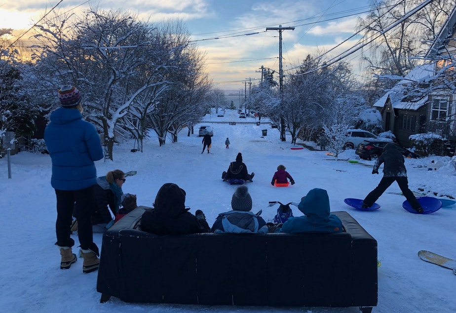 Sean Eley, Renee Grazer and Gabe Goldman set up a couch to sip coffee and watch their kids sled down Juneau in West Seattle.