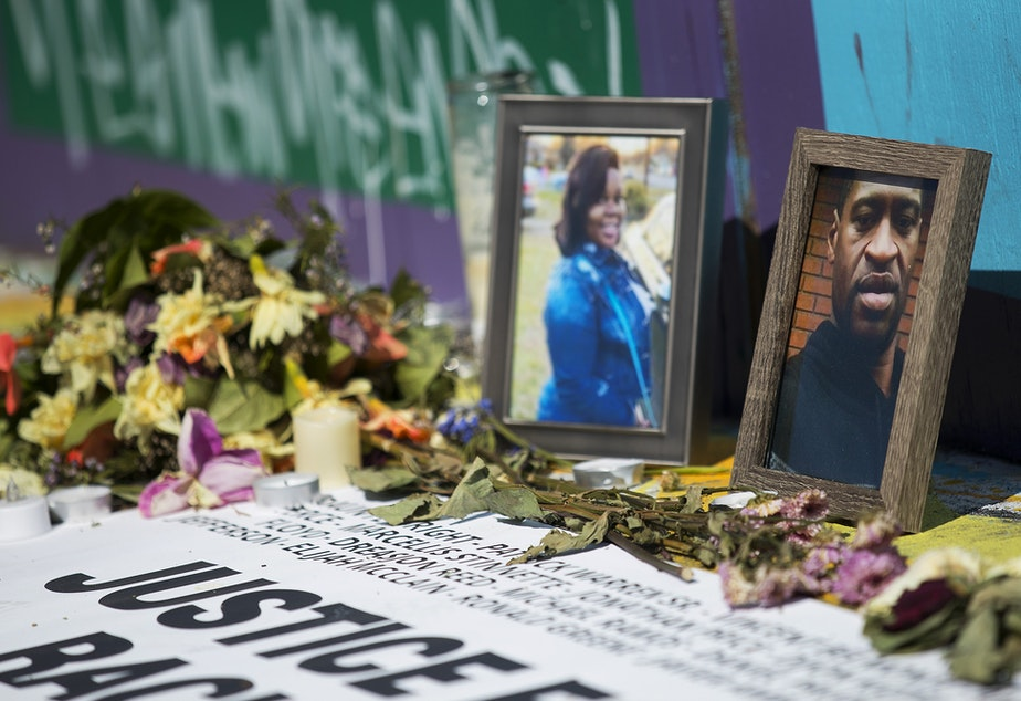 caption: Photographs of George Floyd and Breonna Taylor are shown included in a vigil that remains near the intersection of 11th Avenue and East Pine Street on Tuesday, April 20, 2021, in Seattle. 'Justice For All Victims of Racist Police Terror' read the words, surrounded by candles and flowers as well as the names and photographs of those killed by police.