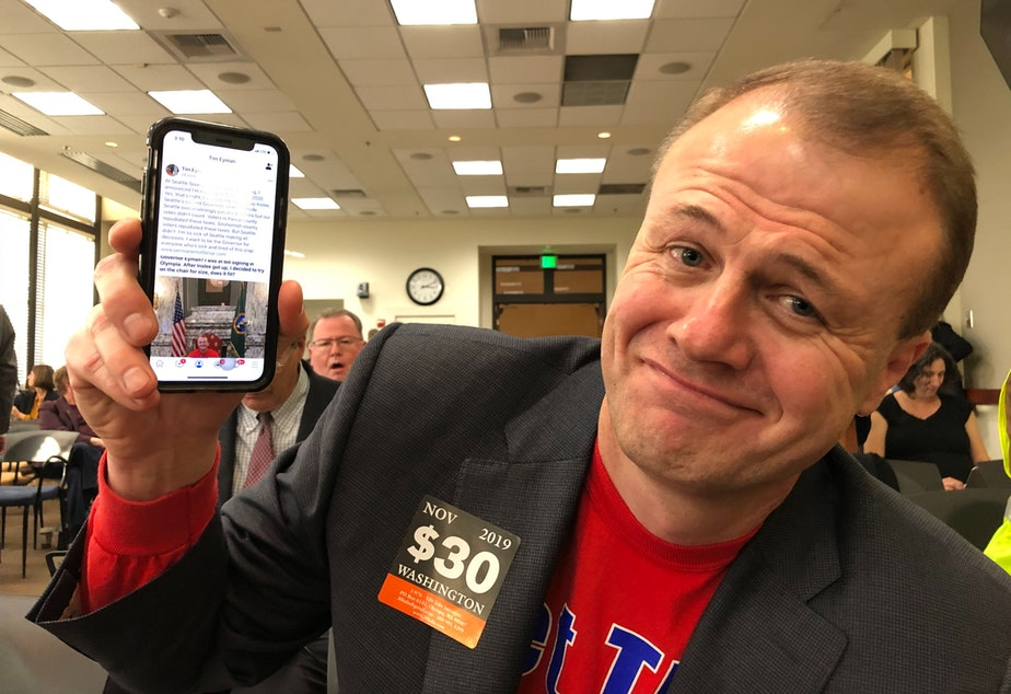 caption: Anti-tax activist Tim Eyman shows off a Facebook post announcing his run for governor.