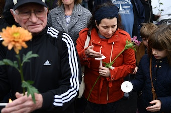 People pay their respects in front of a memorial on Sunday outside of the Tree of Life synagogue in Pittsburgh after a shooting there on left 11 people dead.