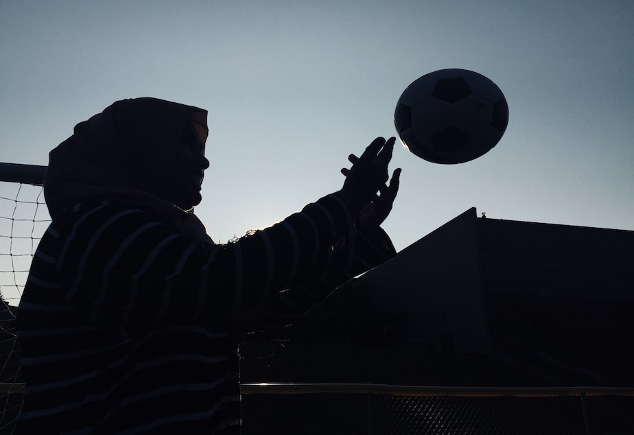 A silhouette of Noor Aamir, tossing a soccer ball.