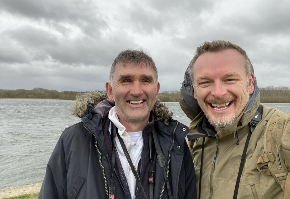 caption: English bird watcher Lee Evans (left) along with THE WILD host Chris Morgan (right) pose while looking for birds.