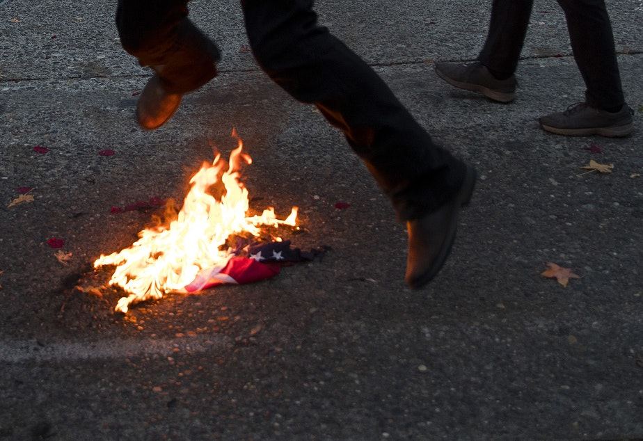 caption: A group of antifascist protesters burned an American flag as hundreds gathered during an impromptu celebration after Joe Biden was officially named the president elect on Saturday, November 7, 2020, at the intersection of 10th Avenue and East Pine Street in Seattle.