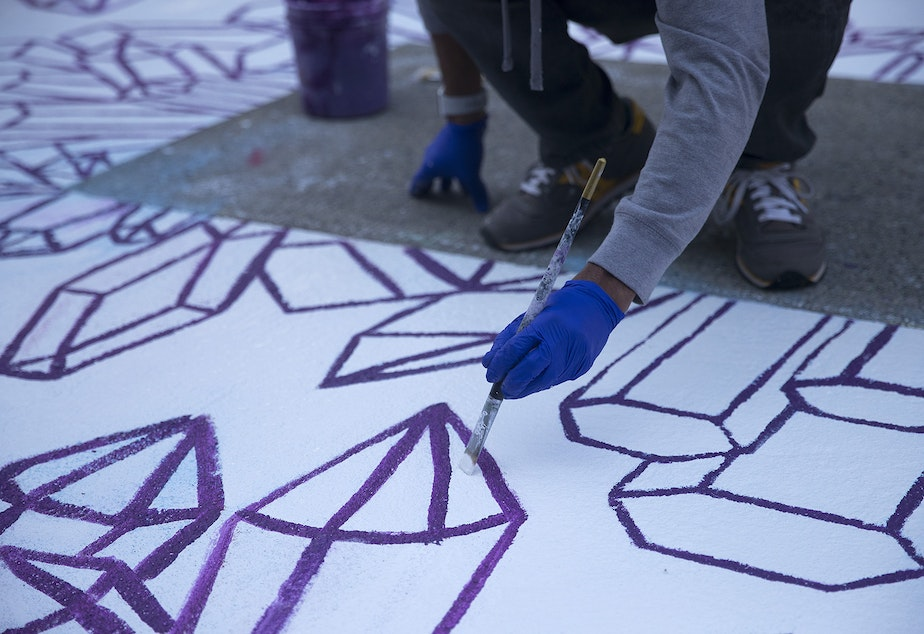caption: Jason Huff helps mixed media artist Future Crystals paint the letter E in the Black Lives Matter street mural on Friday, October 2, 2020, on E. Pine Street in Seattle.