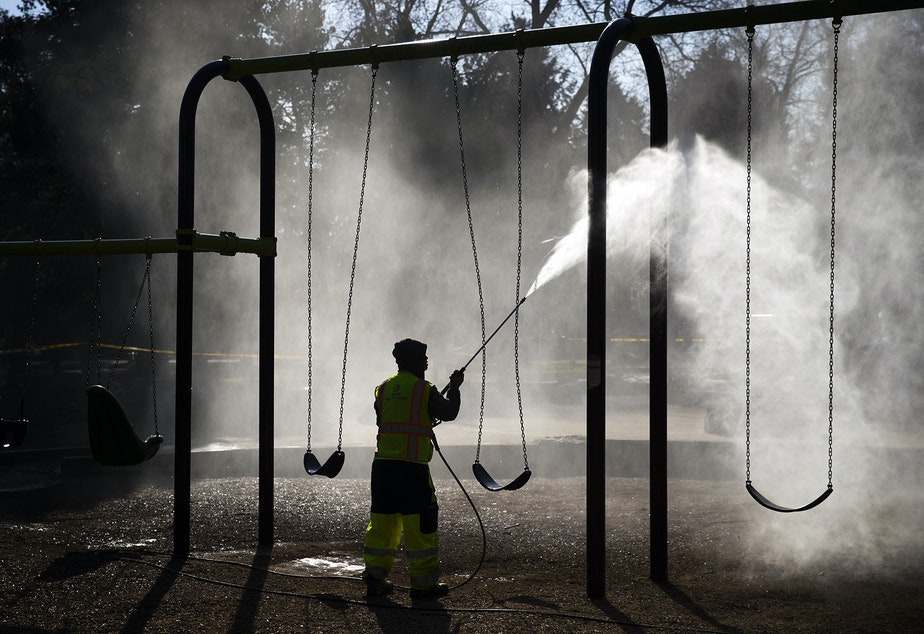 caption: Khai Tran, a utility worker with Seattle Parks and Recreation, sprays water onto a swing-set before a mixture of bleach and water is applied to the West Woodland Park Playground as a result of the coronavirus outbreak on Thursday, March 19, 2020, in Seattle.