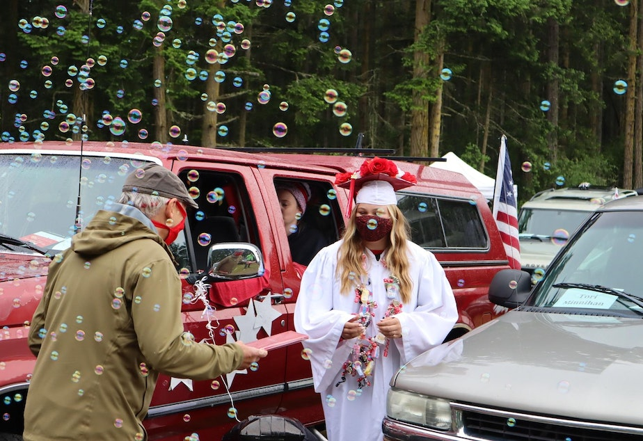 caption: Port Townsend High School senior Torianna Minnihan received her diploma -- and a bubble shower -- at a graduation ceremony held at the local drive-in movie theater on June 12, 2020.