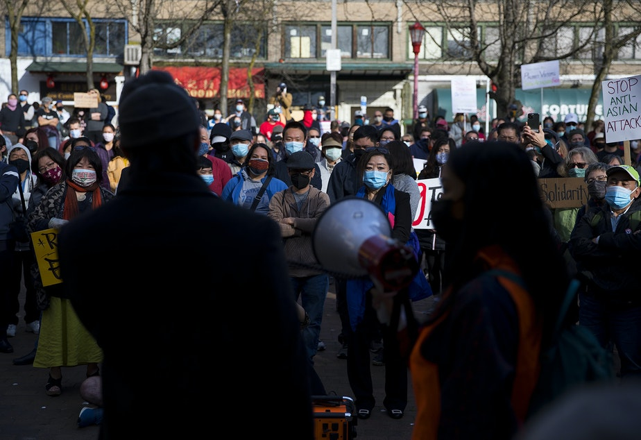 caption: Hundreds gather to listen to speakers during the 'We Are Not Silent' rally and march against hate and violence toward the Asian American Pacific Islander community on Saturday, March 13, 2021, at Hing Hay Park in Seattle.