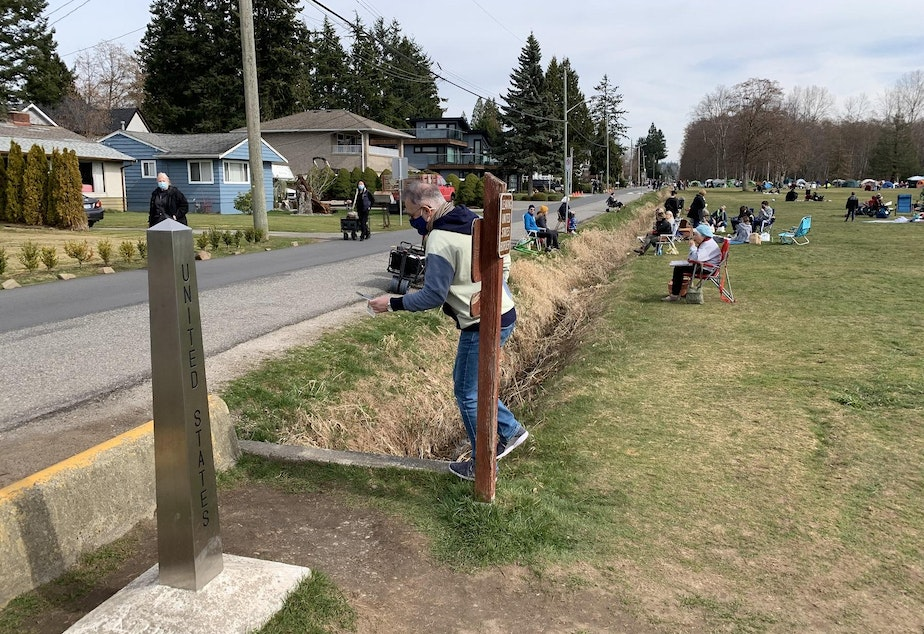 caption: Crossing the border into Peace Arch State Park from Canada, at left, entails stepping across a ditch.