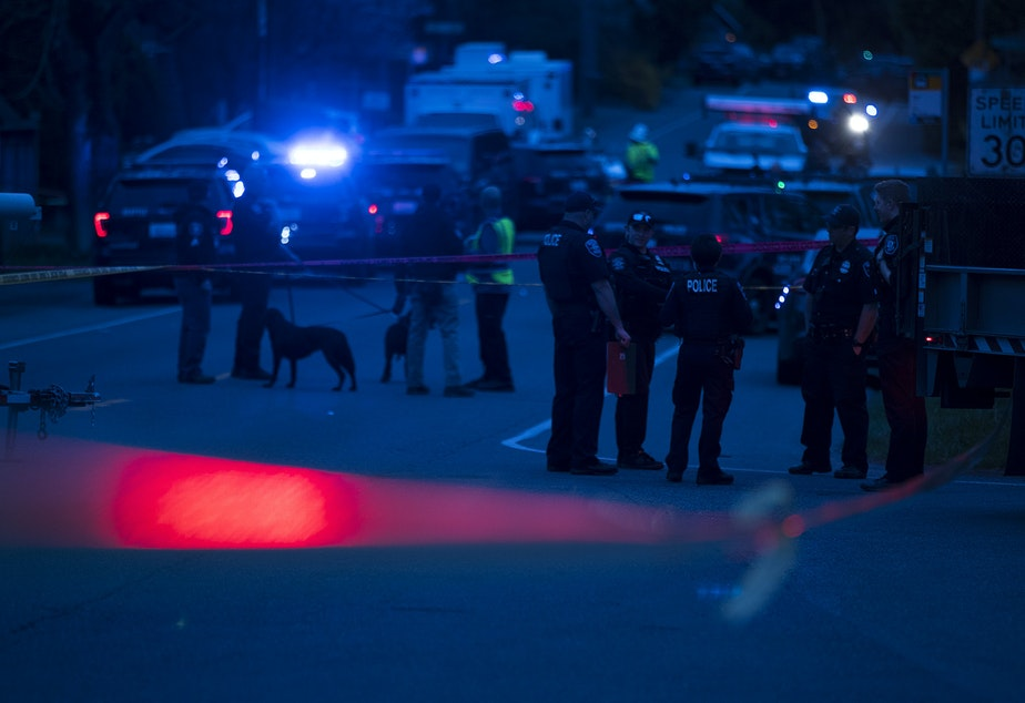 caption: Police investigate the scene of a fatal carjacking and shooting on Wednesday, March 27, 2019, at the intersection of 120th Street and Sandpoint Way Northeast in Seattle.