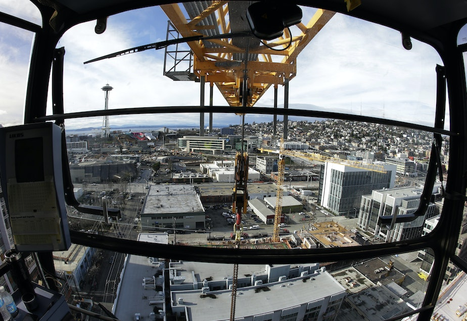 caption: In this Feb. 10, 2015, photo, Seattle's Space Needle and several construction cranes are shown from the operating cab of a 238-foot high construction crane working on a new building in Seattle's South Lake Union neighborhood.