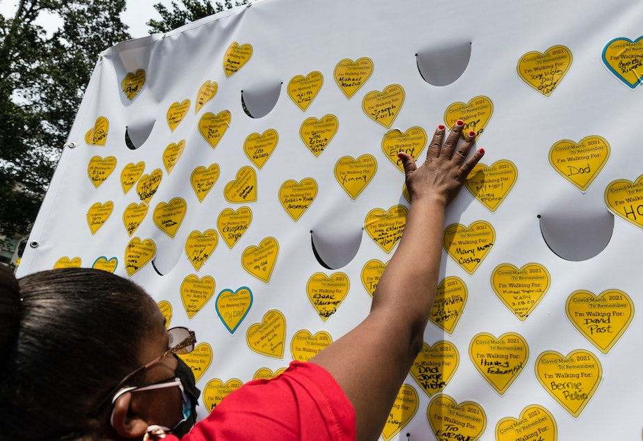 caption: COVID-19 survivors gather in New York and place stickers representing lost relatives on a wall in remembrance of those who have died during the pandemic.