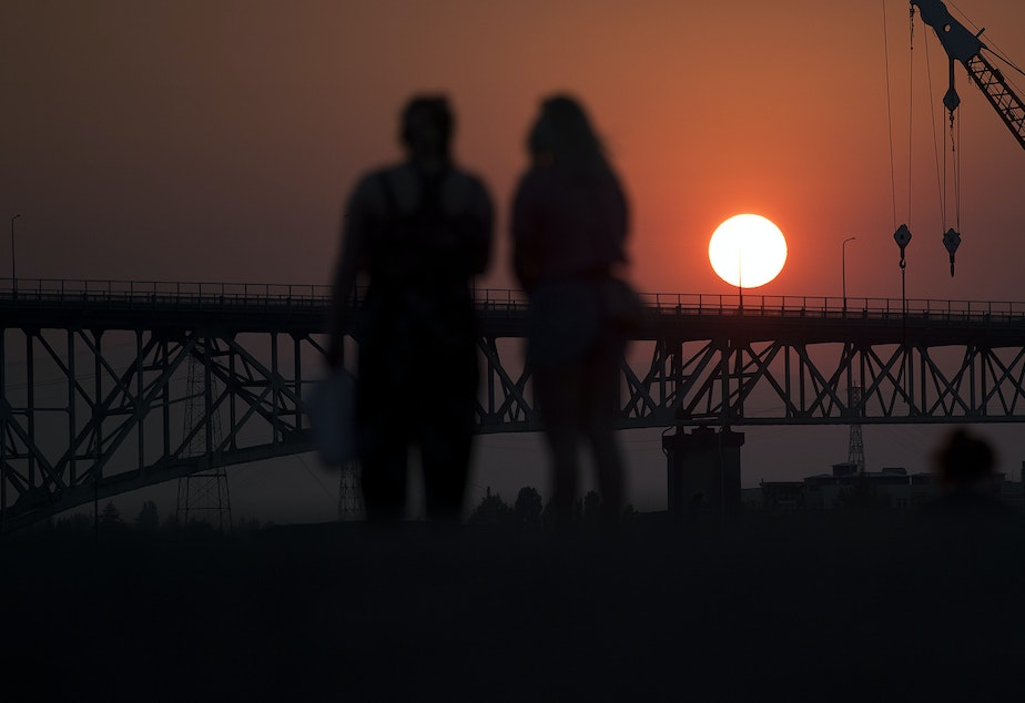caption: People watch as the sun sets from Gas Works Park on Monday, July 30, 2018, in Seattle.