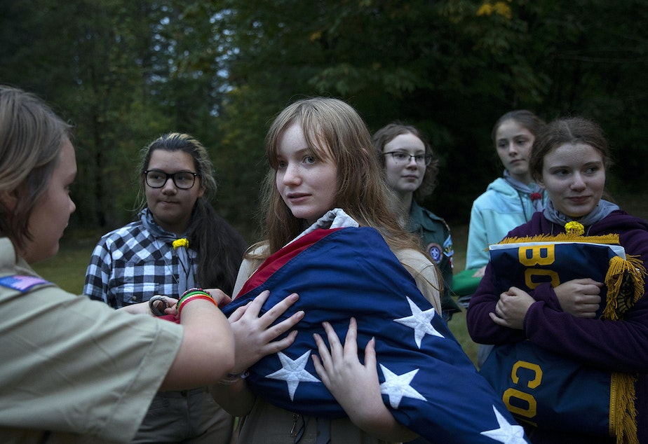 Abigail Matthews, 13, has help from Moriko Peterson, 13, left, after a flag ceremony during the Boy Scouts of America Bootcamp for girls on Saturday, October 6, 2018, at Camp Thunderbird in Olympia.