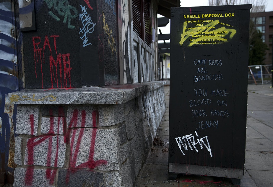 caption: 'Camp raids are genocide, you have blood on your hands Jenny,' is written on the side of a needle disposal box ahead of a scheduled sweep by the Seattle Police Department of a community of people experiencing houselessness on Wednesday, December 16, 2020, at Cal Anderson Park in Seattle.
