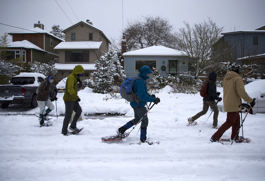 caption: A group of people snowshoe along Northwest 70th Street en route to Golden Gardens on Saturday, February 13, 2021, in Seattle.