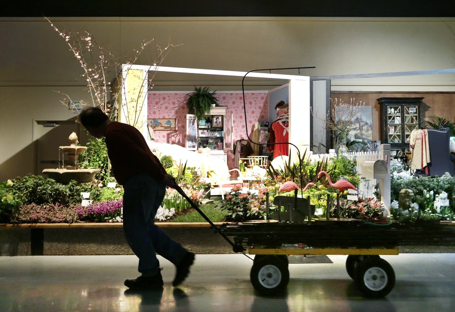caption: A worker pulls a wagon at the Northwest Flower & Garden Show in 2013, in Seattle. The convention center has plans to expand yet again.