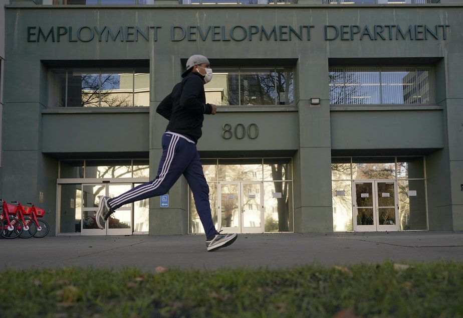 caption: California reported a significant surge in unemployment claims this year for independent contractors, accounting for more than a quarter of all such claims nationally and raising concerns about widespread fraud. Above, a runner passes the office of California's Employment Development Department in Sacramento in December.