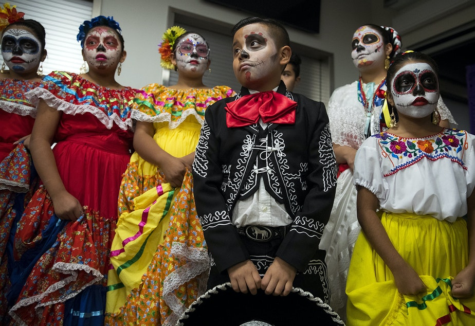 caption: Ivan Galvez, 8, center, stands with other Folklore Mexicano Tonantzin members before performing on Friday, November 2, 2018, during the 14th annual Día de los Muertos celebration at El Centro de la Raza in Seattle.