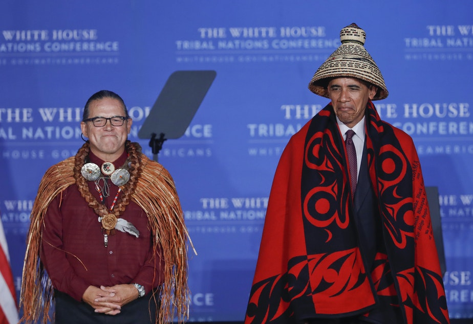 caption: President Barack Obama wears a blanket and hat given to him by Brian Cladoosby, left, President of National Congress of American Indians, during the 2016 White House Tribal Nations Conference, Monday, Set. 26, 2016.