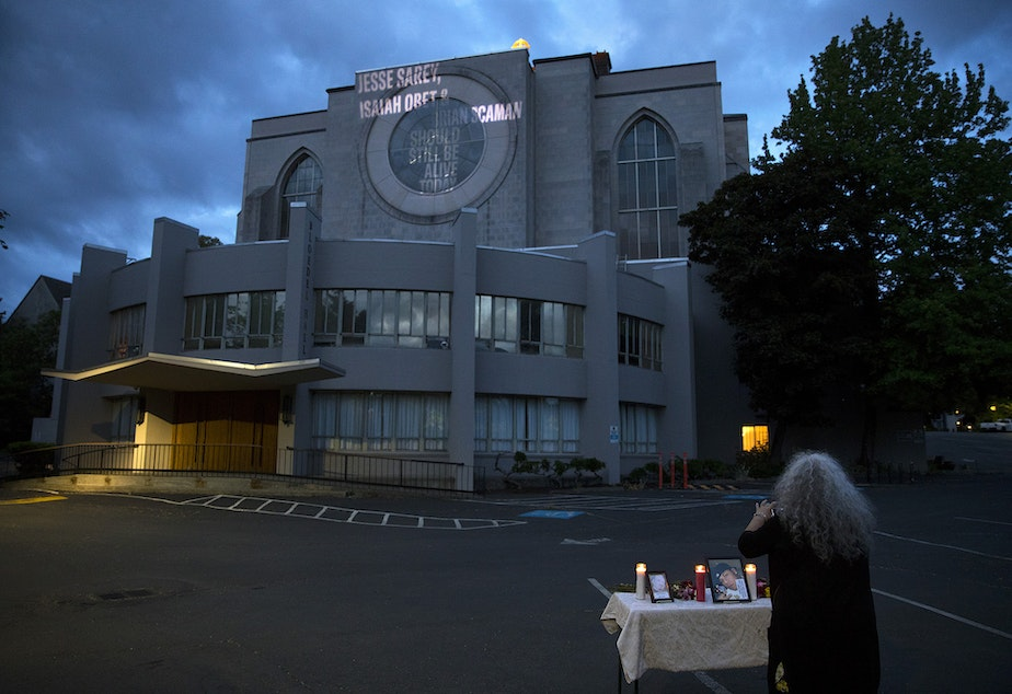 """caption: Elaine Simons takes a photograph of a small vigil set up to honor those killed by Auburn police officer Jeffrey Nelson, including her foster son, Jesse Sarey, on Thursday, June 3, 2021, at Saint Mark's Episcopal Cathedral in Seattle. Family members gathered to see their loved ones names projected onto the side of the building as part of the """"Projecting Justice"""" project."""