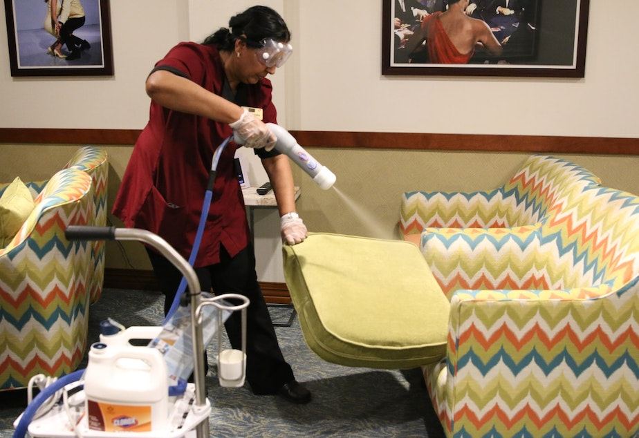 caption: Prem Chandra demonstrates how she sprays down furniture with an atomized disinfectant using the Clorox 360 machine.