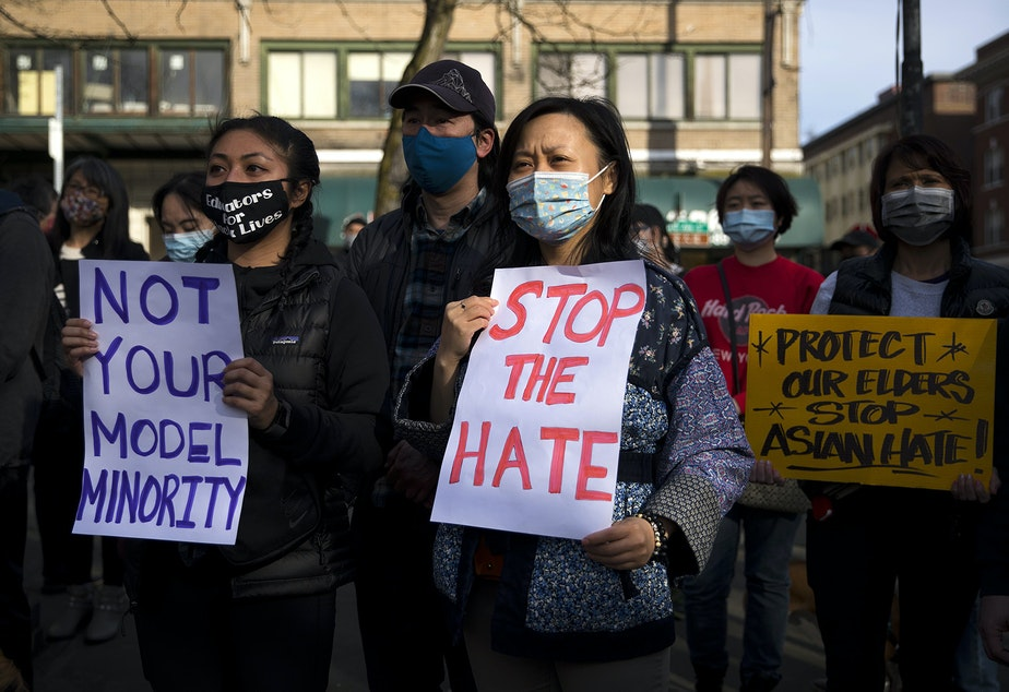caption: Erica Nguyen, left, and Annie Zhou hold signs that read 'Not Your Model Minority' and 'Stop The Hate' while attending the 'We Are Not Silent' rally against anti-Asian hate and violence on Saturday, March 13, 2021, at Hing Hay Park in Seattle. Several days of actions are planned by rally organizers in the Seattle area following recent attacks and violence against Asian Americans and Pacific Islanders.